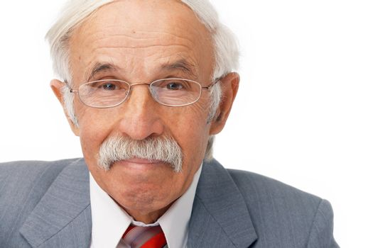 Close-up portrait of an elder businessman looking at you and smiling.