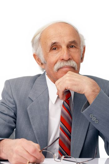 Close-up portrait of an elder businessman sitting thoughtful over white.