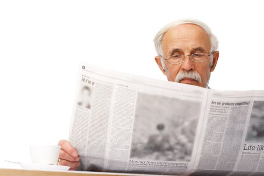 Portrait of an elder businessman reading a newspaper with a cup near him.