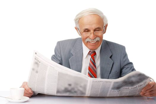 Portrait of an elder happy man reading a newspaper with a cup near him.