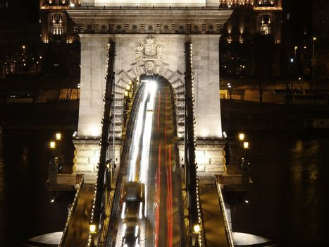 Chain bridge at night time with cars.