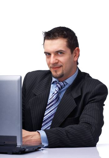 Happy young businessman working on laptop, looking at you over white.