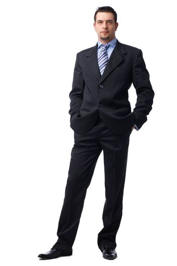 Portrait of a confident young  businessman with hands in pockets on white background.
