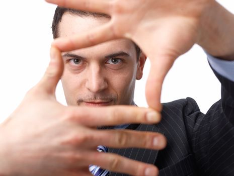 Close up portrait of a confident young businessman making a frame shape with his hands over white background
