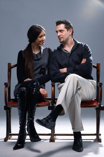 Young couple sitting on a theatrical bench looking at each other.