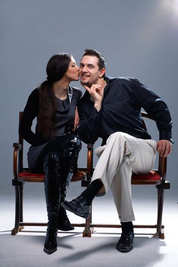 Young woman kissing a man in a cheek on the bench.