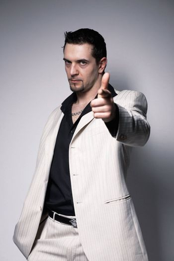 Portrait of a young confident man pointing at you  over white.