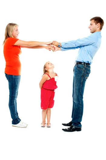 Playful parents holding hands while cute daughter keenly watches them