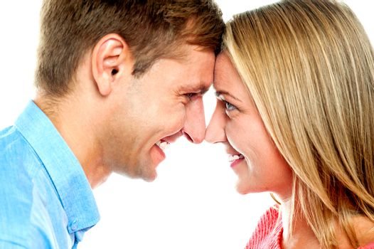 Smiling couple posing. Foreheads touching