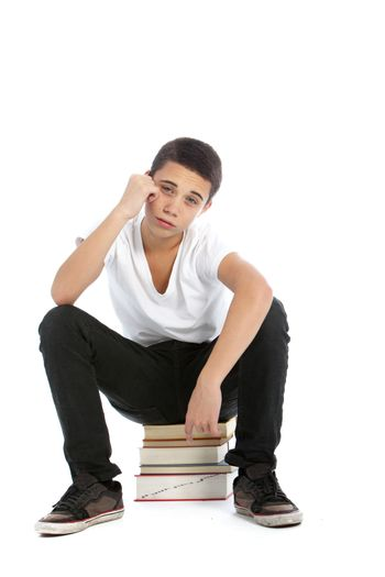 Dejected teenaged boy with his textbooks