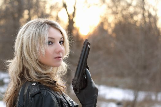 Provocative young woman with a gun