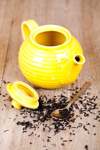 yellow teapot with spoon and tea