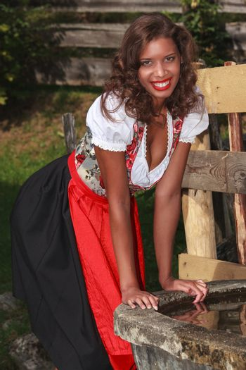 Bavarian girl in costume, smiling at the water trough