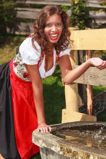 Young beauty in Bavarian costume has fun at the fountain