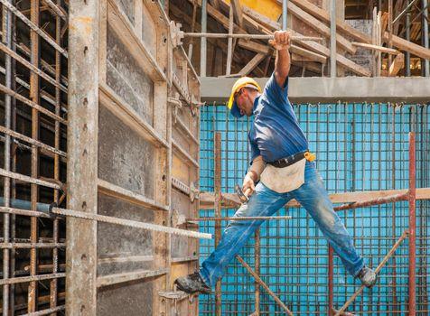 Construction worker balancing between scaffold and formwork fram