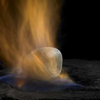 studio shot of a pebble and flames in dark back