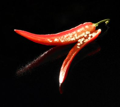 studio shot of a red sliced chili in black reflective back
