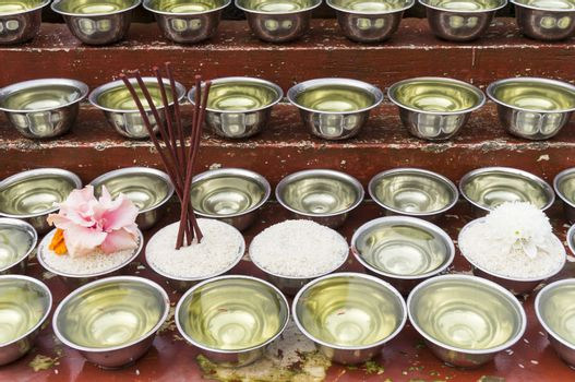 many small bowls with water and rice around a temple in nepal