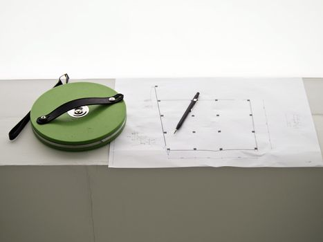 A measuring tape and a pencil over a construction drawing of a house