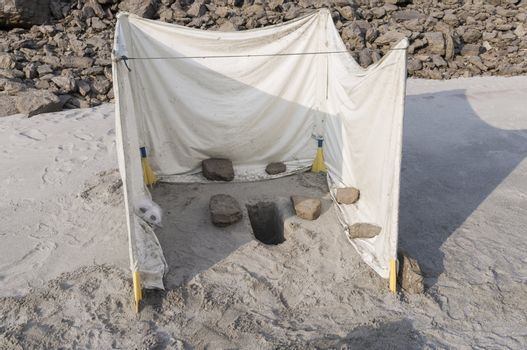 toilet used at an adventure trip. whole in the sand with a plastic foil around