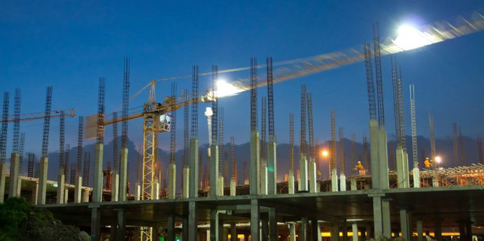 Industrial construction cranes and building at night