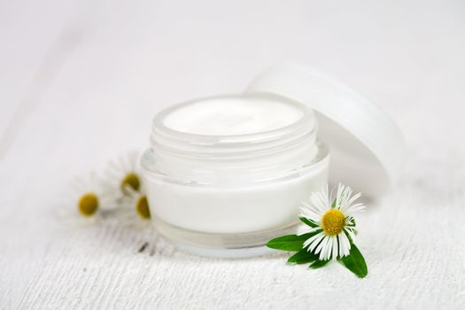 container with cream and camomiles