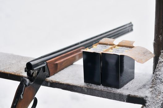 Hunting rifle and bullets. On winter background.