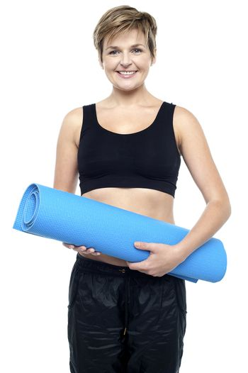 Health conscious woman holding blue exercise mat