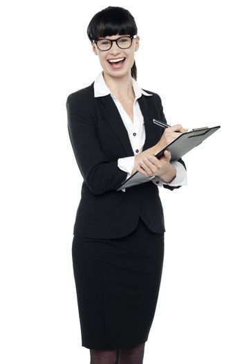 Charming businesswoman writing on notepad