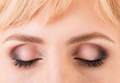 Women's closed eyes closeup coated with makeup and eyelashes glued