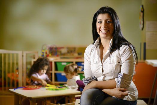 happy teacher with children eating in kindergarten