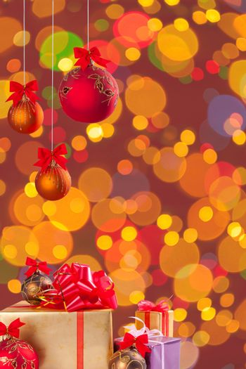 Gifts and cristmas balls on ribbon on festive background