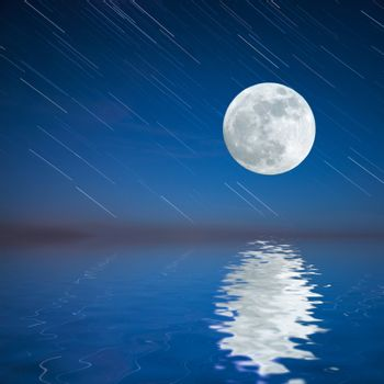Night landscape with moon reflection in water and sky background with startrails