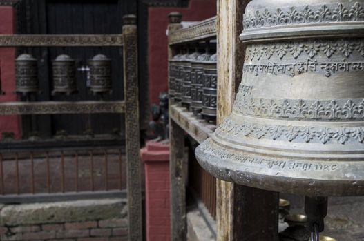 bell in foreground and prayer wheels in kathmandu, nepal