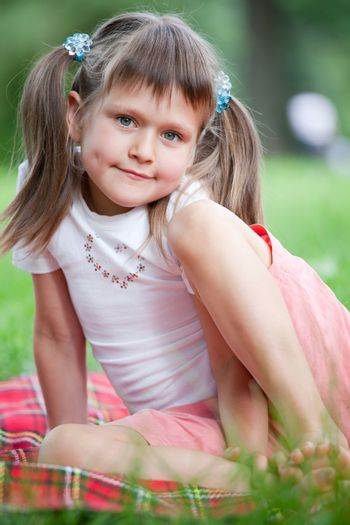 Portrait of little cute blond girl preschooler with ponytails sitting on the red plaid on green grass in summer