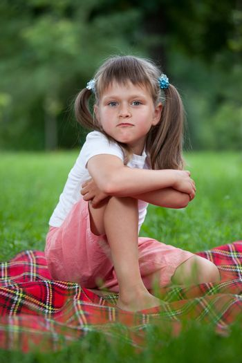 Portrait of little militant blond girl preschooler with ponytails sitting in closed pose on the red plaid on green grass in summer