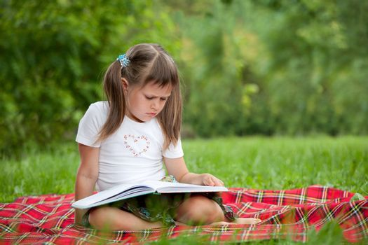 Little studious girl preschooler is reading open book and sitting on the red plaid on green grass in summer park