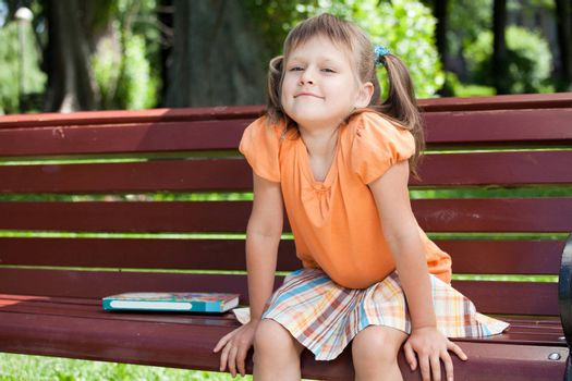 Little cute smiling girl preschooler with open book who is sitting on the wooden bench in summer park