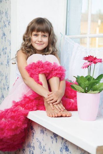 Young amazing joyful girl teenager close-up dressed luxuriant wavy skirt with frill sitting with outstretched legs on white windowsill inside room near fresh natural flower in flowerpot