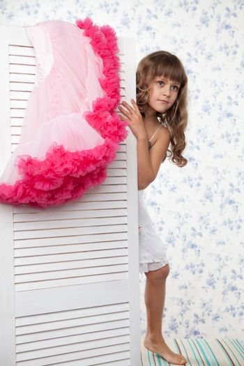 Young blond girl child with long wave hair looks out the folding screen when change of clothes