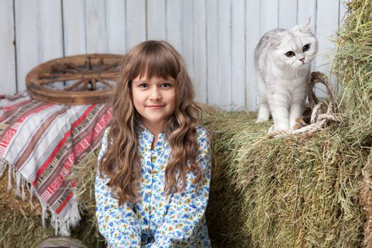 Portrait of sincere little blond girl villager and white cat on hay stack in wooden hayloft