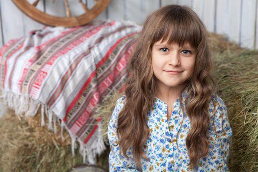 Portrait of friendly little blond girl villager in wooden hayloft with vintage decoration