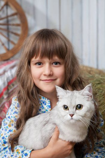 Portrait of little sincere friendly blond girl villager sitting with white cat in hands in wooden barn
