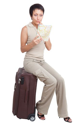 Thinking young tourist haircut woman looking at city map dressed buff trouser suit sits on the brown traveling suitcase isolated