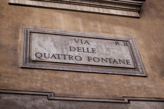 Marble street sign via Quattro fontane (four fontauns) on the painted stone wall in Rome, Italy