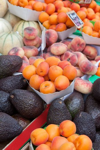 Plates with ripe orange apricot, fig peach, purple avocados, melons at fruit market