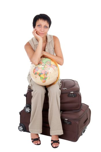 Smiling young tourist haircut woman dressed buff trouser suit sits on the  brown traveling suitcase with globe isolated