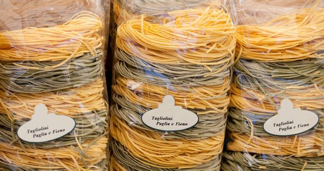 Packed italian egg yellow and spinach pasta tagliatelle at store
