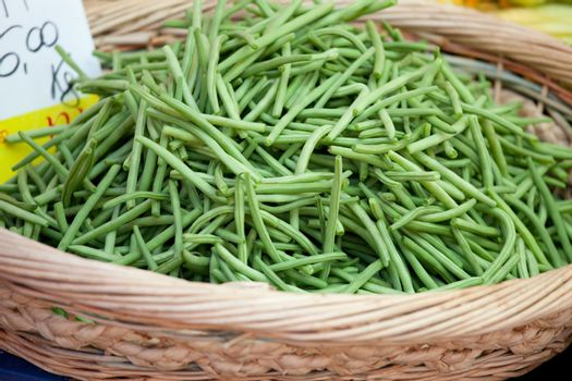 Fresh pods of vegetable green string beans macro in woven basket close-up at the table