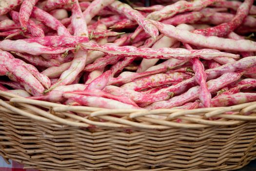 Fresh pods of vegetable speckled red string beans macro in woven basket close-up at the table